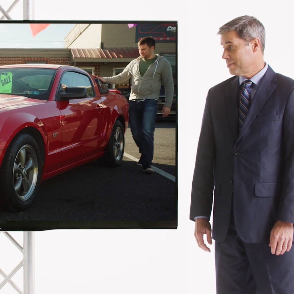 Investigator looking at TV showing an insurance fraudster eyeing brand new red car.
