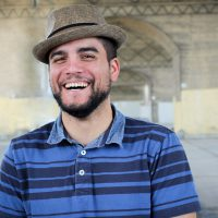 Carlos Centeno smiling as he wears is tan-colored fedora.