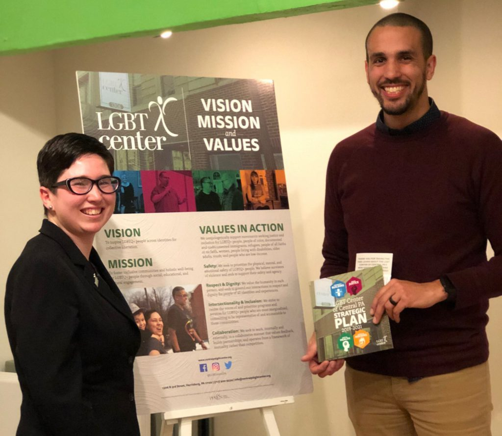 Josh and Amanda posting with the brochure and poster we created for the LGBT center.