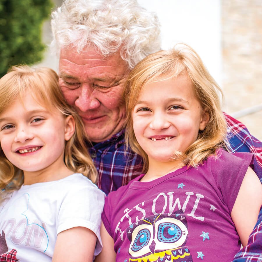 Grandfather with his two young twin grandaughters.