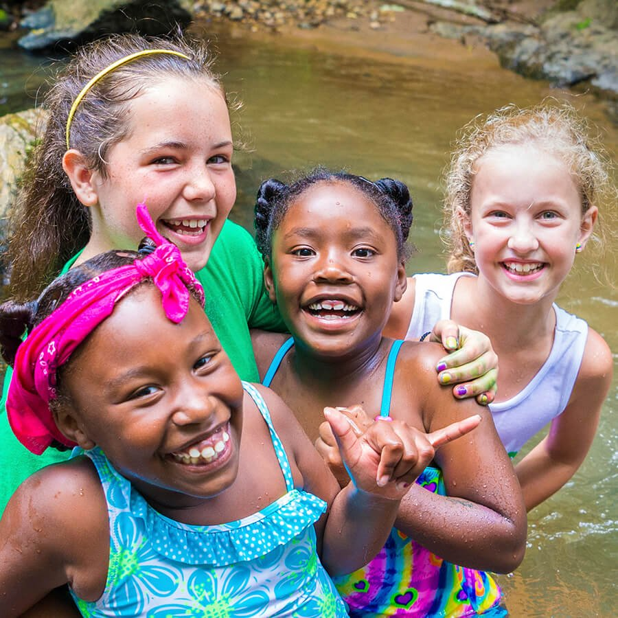 4 young girls hugging and smiling at the camera as they play in a creek.
