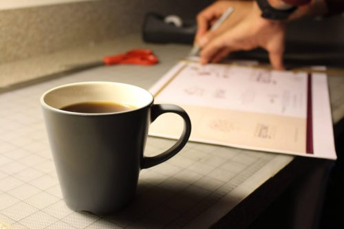 Close-up of designer's hands trimming a design on a cutting mat near a coffee cup.