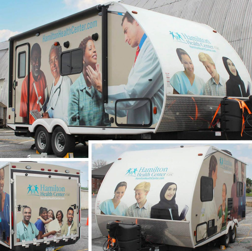 Mobile trailer wrapped in graphics of health professionals and patients.