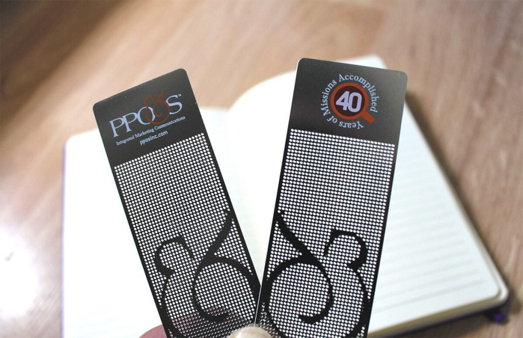 Close-up of bookmarks: They're made of light-gray metal with tiny circular cuts that show the ampersand in the PPO&S logo.
